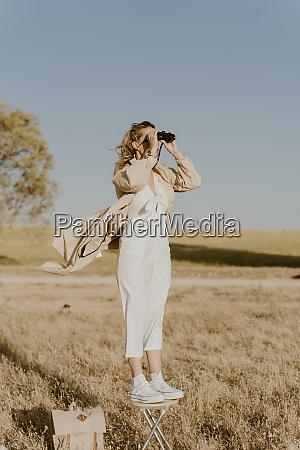 female traveller looking through binoculars