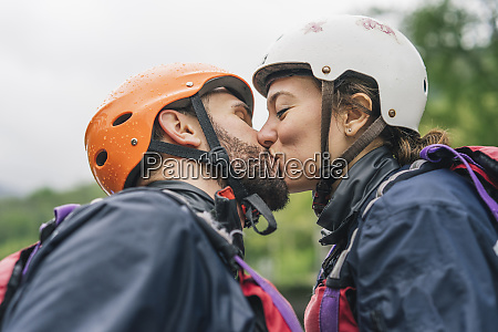 couple wearing safety helmets kissing outdoors