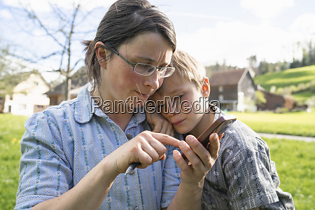 mother with son using portable device