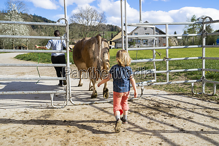 daughter with mother and cow on