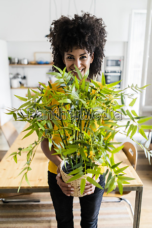 portrait of smiling woman holding plant