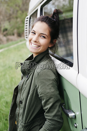 laughing young woman leaning on camper