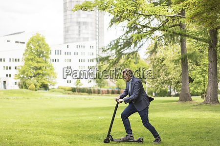businessman using e scooter on a