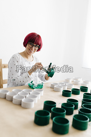 woman painting a roll of cardboard