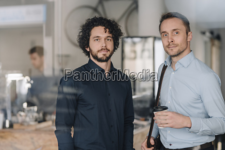 two businessmen standing in a coffee