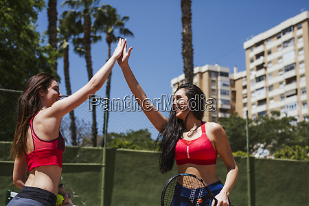 two happy female tennis players high