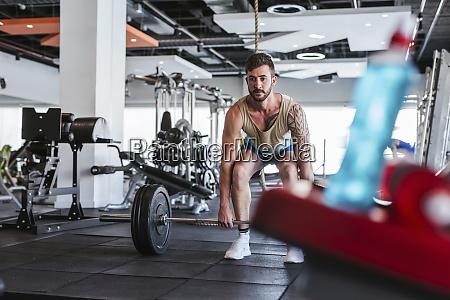 kickboxer in fitness studio weight lifting