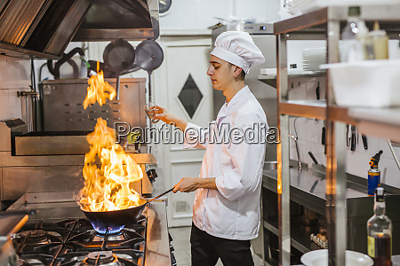 junior chef with pan of flames
