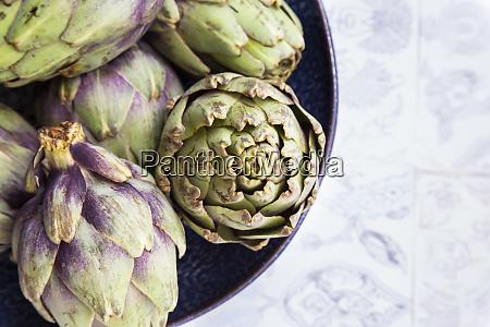 italian bio artichokes in bowl from