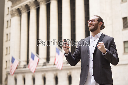 happy young businessman with cell phone