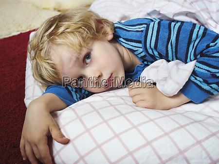 portrait of little boy lying on