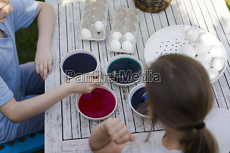two girls dyeing easter eggs on