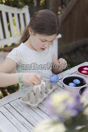 girl dyeing easter eggs in garden