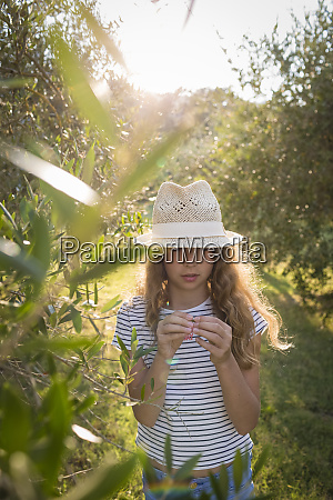 girl with straw hat standing in