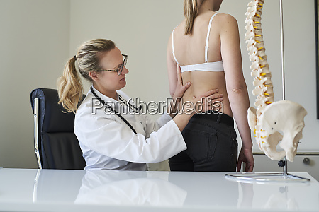 female doctor examining back of patient