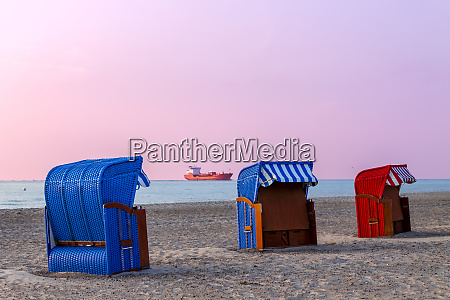 three hooded beach chairs at sunset