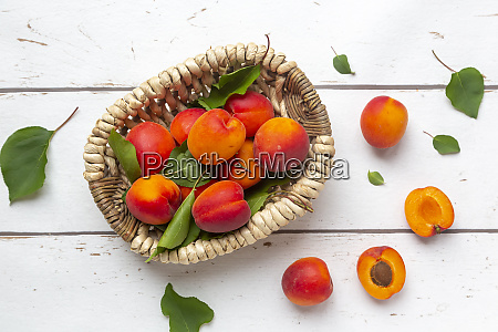 apricots in basket on white wood
