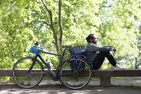 young man with bicycle relaxing on
