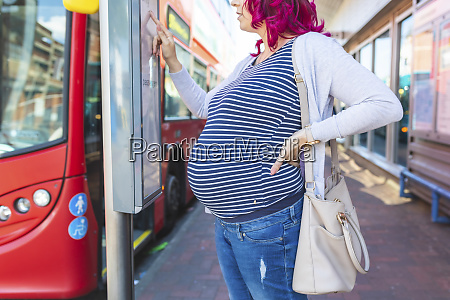 pregnant woman at bus stop checking