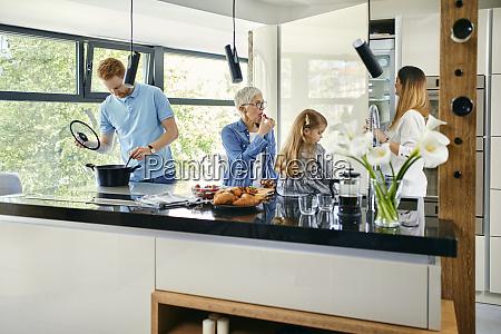 three genaration family preparing food in