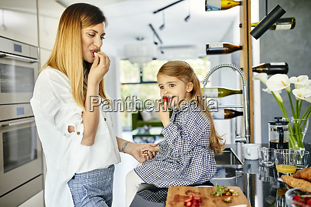 mother and daughter eating strawberries in