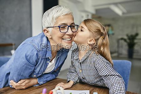 grandduafZghter kissing grandmother painting colouring book