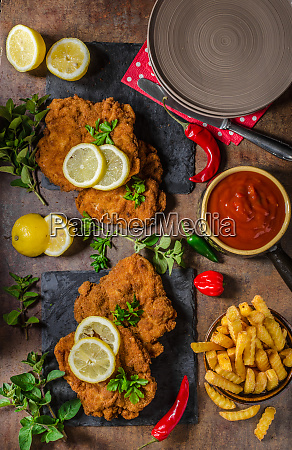 schnitzel with fries salad and herbs