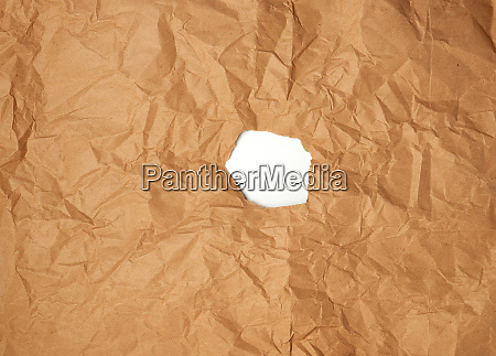 round torn hole in brown paper