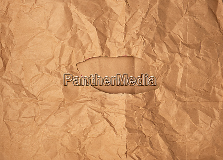 crumpled brown sheet of paper with