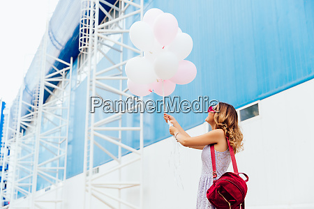 trendy girl holds air balloons with