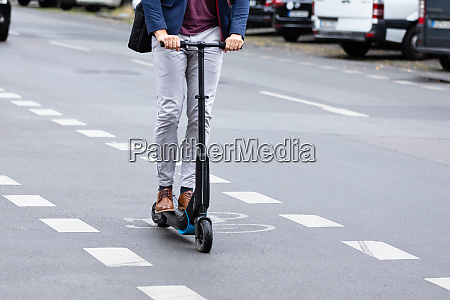 businessman riding an electric scooter on