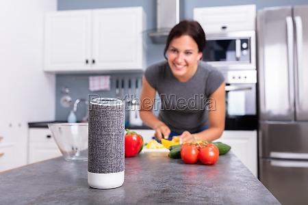 woman listening music on wireless speaker