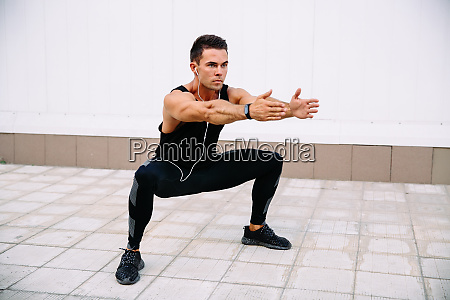 athlete doing squats outdoors