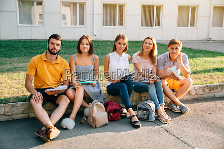 happy college students with books sitting