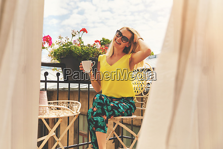 attractive smiling girl relaxing on balcony