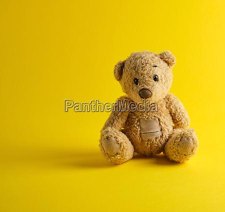 teddy bear sitting on a yellow