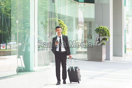 businessman with luggage walking to airport