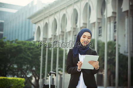 muslim woman working on table pc