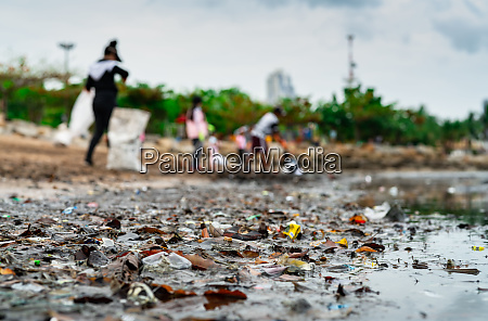 blurred of volunteers collecting garbage beach