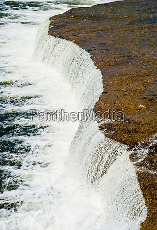 wide flat waterfall flowing into river