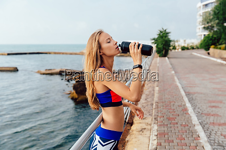 fit sportswoman drinking a water after