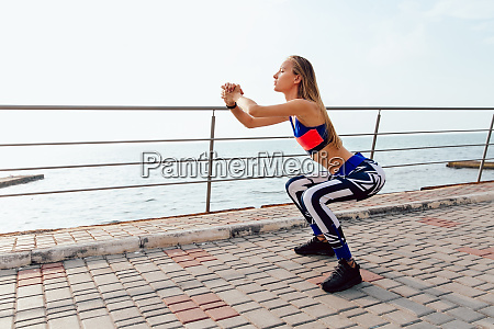 sportswoman doing squats during practice outdoors