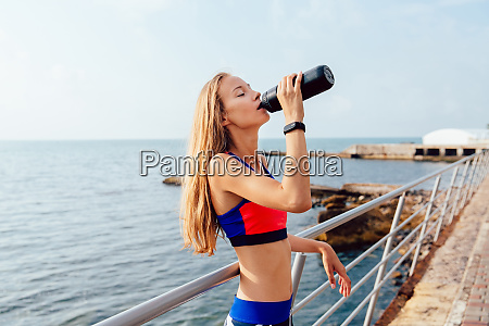 blonde sportswoman drinking a water after