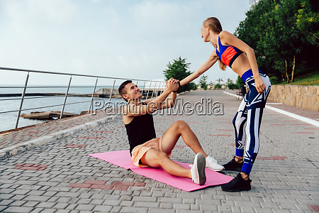 sportive girl helps a sportsman to