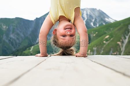 little girl standing on her head