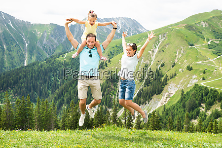 happy family jumping in mountains