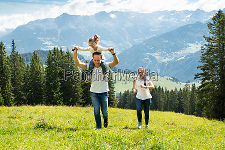 family with daughter running on field