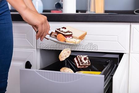 woman throwing food in trash bin
