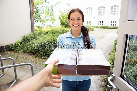 woman delivering donuts to man