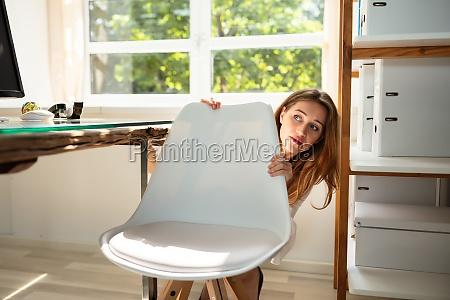 afraid businesswoman peeking behind chair